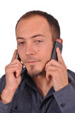 Bored busy guy with two cellphones Stock Photo