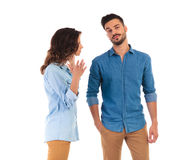 Bored casual man listening to his woman talk at him. Bored casual men listening to his women talk at him, he is standing with hands in pockets on white Royalty Free Stock Images