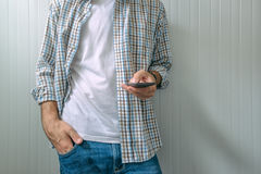 Bored casual man using mobile phone Royalty Free Stock Photography