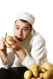 Bored chef peeling potatoes Royalty Free Stock Photos