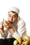 Bored chef peeling potatoes royalty free stock photos