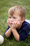 Bored child. Child laying on grass with bored expression (boredom Royalty Free Stock Image