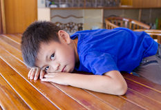 Bored child. Bored expression child laying on table dont want to play Royalty Free Stock Photography