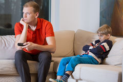 Bored child and father is watching TV Stock Photo
