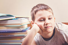 Bored child between piles of books Stock Images