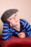 Bored Child Wearing Flat Cap. A bored young boy child wearing flat cap and striped shirt Royalty Free Stock Photography