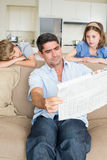 Bored children looking at father reading newspaper Royalty Free Stock Photo