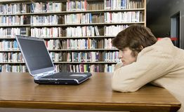 Bored College Student Looking At Laptop Stock Photo
