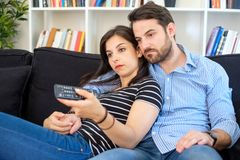 Bored couple after binge watching streaming series. Lazy and bored couple at home sitting on sofa watching tv royalty free stock images