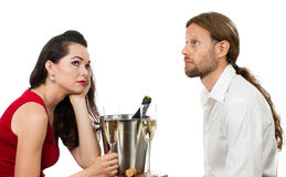Bored couple on a date. A bored couple out on a Champagne date avoiding eye contact. Isolated on white Royalty Free Stock Photos