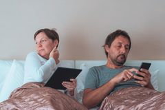 Bored couple, husband and wife in bedroom. Using personal electronics devices royalty free stock photos