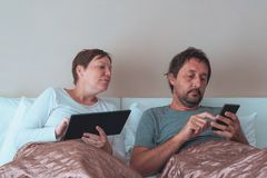 Bored couple, husband and wife in bedroom Royalty Free Stock Images