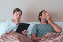 Bored couple, husband and wife in bedroom Stock Images