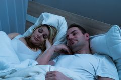 Bored couple lying in bed Royalty Free Stock Image