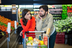 Bored couple with shopping trolley in organic section Stock Image