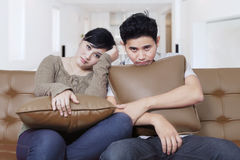 Bored couple sit on a couch Royalty Free Stock Photos
