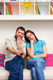 Bored couple watching TV. Bored couple sitting on the sofa and watching TV Stock Image