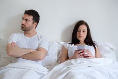 Bored couple and worried man by his wife mobile phone addiction Stock Images