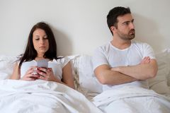Bored couple and worried man by his wife internet addiction Stock Images