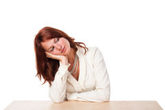 Bored and curious woman in beige. Slightly curious woman in a beige shirt sitting behind the table. On white background royalty free stock photo
