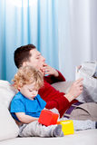 Bored dad reads the newspaper Stock Images