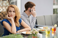 Bored on date. Pretty young women is bored when her boyfriend making business call Royalty Free Stock Photography