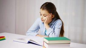 Bored de lezingsboek of handboek van het schoolmeisje thuis stock footage