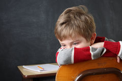 Bored and Discouraged Student. A young boy sits with his head in his arms on the back of his chair Royalty Free Stock Photos