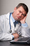 Bored doctor sits at laptop Stock Photography