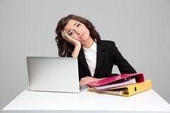 Bored droevige jonge vrouw gebruikend laptop en werkend met documenten royalty-vrije stock afbeeldingen