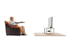 Bored elderly man sitting in an armchair and watching television Stock Photography