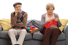 Bored elderly man sitting on a sofa next to an elderly woman kni Royalty Free Stock Photography