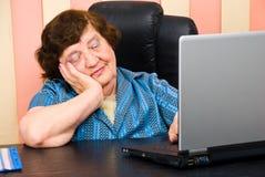 Bored elderly woman in office stock photos