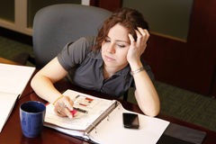 Bored employee. A bored business woman sits at her desk royalty free stock photography