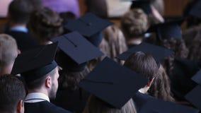 Bored en vermoeide gediplomeerden die diploma het toekennen op ceremonie, de schuld van de studentenlening letten stock footage