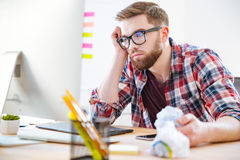 Bored exhausted man sitting on workplace and looking at monitor. Bored exhausted bearded young man in checkered shirt sitting on workplace and looking at monitor Royalty Free Stock Images