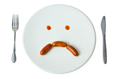 Bored face sausage on white dish Stock Photography