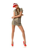 Bored Fashion Model. Beautiful young woman in gold mini dress, red sun visor and red high heels posing and looking away, Full length studio shot isolated on Royalty Free Stock Photography