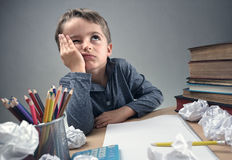 Bored and fed boy up doing his homework. Thinking child bored, frustrated and fed up doing his homework stock photos