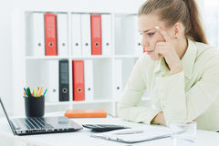 Bored female office worker sits at her desk and looks at computer screen. Royalty Free Stock Photos