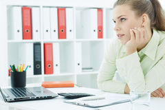 Bored female office worker sits at her desk and looks into the distance. Royalty Free Stock Images