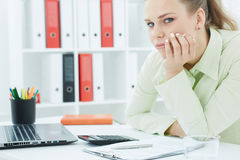 Bored female office worker sits at her desk in the office. Busy schedule concept Stock Images