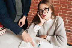 Bored female student listening to coach close-up. Portrait of tired grimacing girl in glasses ignoring teacher. Education, boredom, private lessons, extra Stock Photo