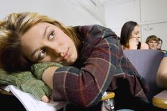 Bored Female Student Relaxing On Desk Royalty Free Stock Images