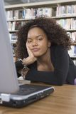 Bored Female Student Sitting At Library Desk Stock Photography