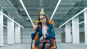 Bored female worker throws confetti while sitting in an office chair. 4K stock video