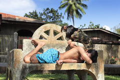 Bored Filipinos taking nap. Two bored lazying young Filipinos taking a nap in the afternoon sun on a bench in a small Mindanao rural village Stock Image