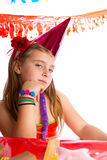 Bored gesture blond kid girl in party birthday hat. Bored gesture blond kid girl in party with birthday hat portrait on white Royalty Free Stock Photography