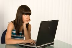 A bored girl. A cute bored girl with laptop Royalty Free Stock Photography