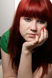 Bored girl. A portrait of a bored 18 year old girl with long red hair, freckles and pierced eye-brow. Face on a hand with red-polished nails Royalty Free Stock Photo